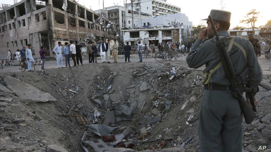 FILE - Security forces stand next to a crater created by a massive explosion that killed over 150, according to the Afghan president, in front of the German Embassy in Kabul, Afghanistan, May 31, 2017. The Taliban's second in command and head of the