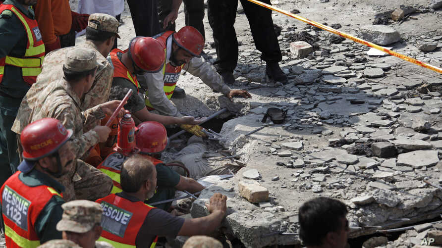 Pakistani Army troops and rescue workers struggle to recover a body in the rubble at the site of a suicide bombing in Shadi Khan, about 80 kilometers (50 miles) northwest from Pakistani capital, Aug. 16, 2015.