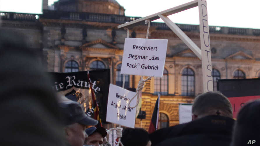 """FILE - A demonstrator carries a mock gallows with nooses, marked """"Reserved for Angela Merkel"""" and """"Reserved for Sigmar Gabriel,"""" her deputy, in a protest by PEGIDA (Patriotic Europeans against the Islamization of the West) in Dresden, Germany, Oct. 1"""