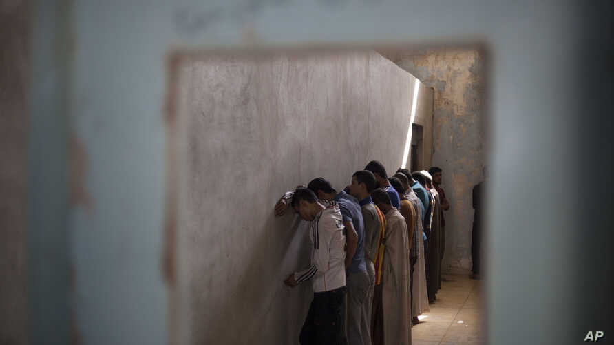 FILE - Displaced men from Hawija stand facing a wall in order not to see security officers, who will try to determine if they were associated with the Islamic State group, at a Kurdish screening center in Dibis, Iraq, Oct. 3, 2017.
