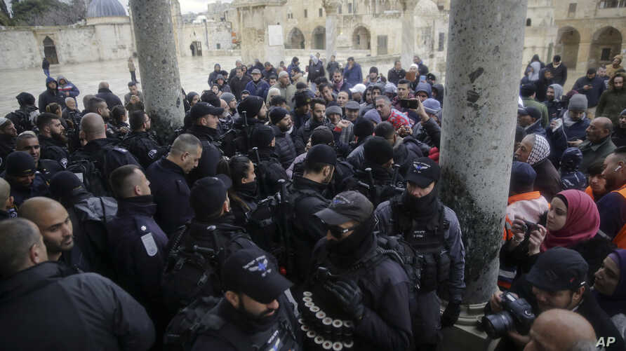 Israeli police stand at the door to the Dome of the Rock mosque confronted by Palestinians, Jan. 14, 2019.