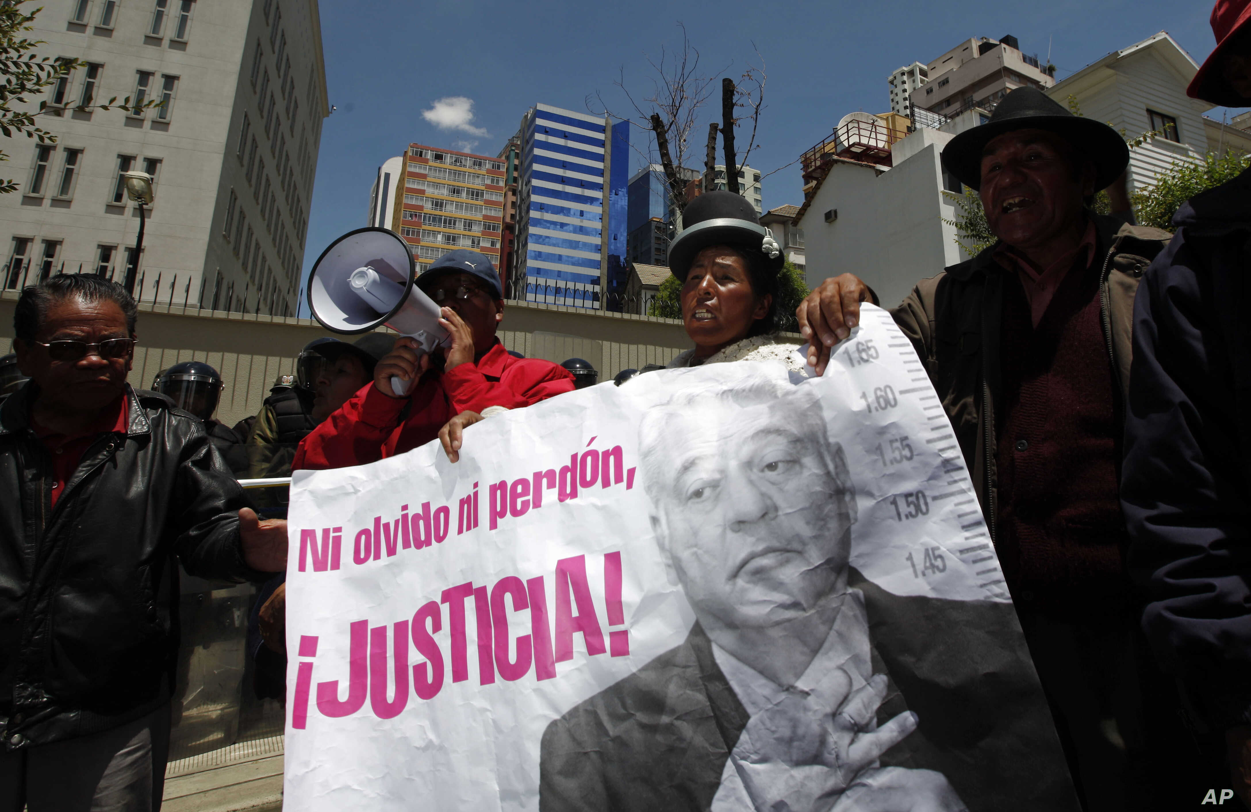 """FILE - Protesters hold a banner showing an image of Bolivia's former President Gonzalo Sanchez de Lozada that reads in Spanish """"Neither forget nor forgive, Justice!"""" during a protest demanding his extradition outside the U.S. embassy in La Paz, Boliv"""