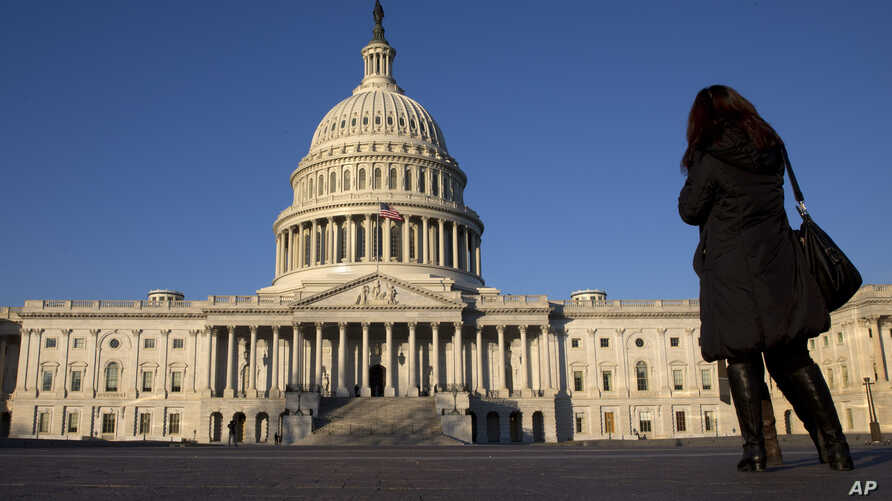 FILE - A woman looks at the U.S. Capitol in Washington.