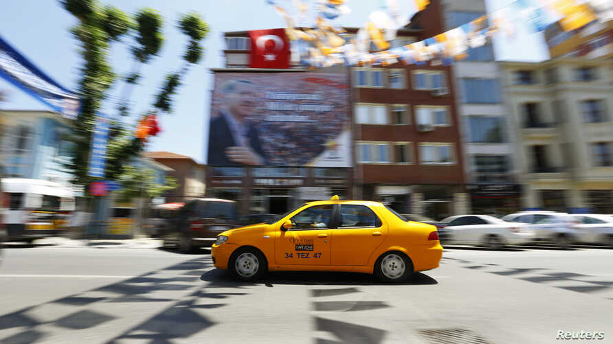FILE - A yellow taxi drives past a poster depicting Turkey's Prime Minister Tayyip Erdogan in Istanbul.