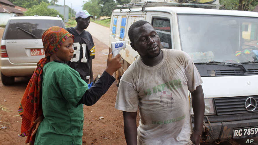A health worker (l) uses a thermometer to screen a man at a makeshift road block run by Guinean security forces outside the town of Forecariah, Guinea, Sept. 7, 2014.
