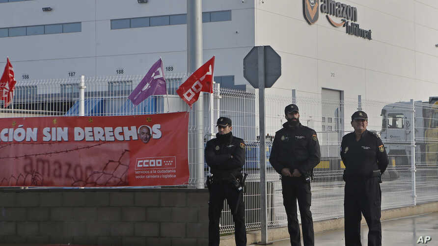 Police guard the entrance of the main Amazon Logistics Center where goods are stored for distribution, on the outskirts of Madrid, Spain, Friday Nov. 22, 2018.