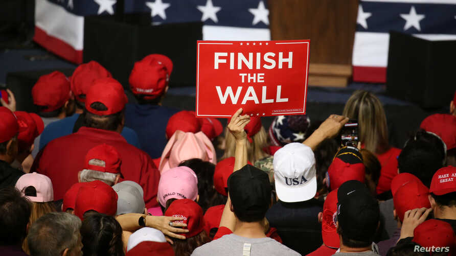 A supporter holds a placard as U.S. President Donald Trump speaks during a rally at El Paso County Coliseum in El Paso, Texas, Feb. 11, 2019.