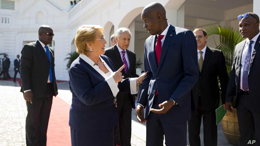 Haiti's President Jovenel Moise, right, talks with Chile's President Michelle Bachelet as she leaves the National Palace after their meeting in Port-au-Prince, Haiti, March 27, 2017.