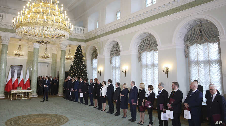 Polish Prime Minister Mateusz Morawiecki, left, along with the new Ministers of his cabinet speaks during the swearing-in ceremony at the Presidential Palace in Warsaw, Poland, Jan. 9, 2018.