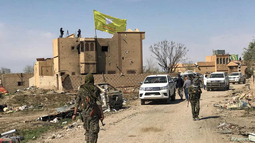 FILE - A Syrian Democratic Forces flag flutters on a damaged building in the twon of Baghuz, Syria, March 23, 2019.