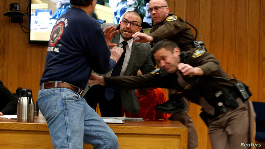 Randall Margraves, left, lunges at Larry Nassar (wearing orange) a former team USA Gymnastics doctor who pleaded guilty in November 2017 to sexual assault charges, during victim statements of his sentencing in the Eaton County Circuit Court in Charlo