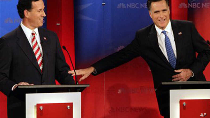 Republican presidential candidates former Massachusetts Gov. Mitt Romney, right, reaches out to former Pennsylvania Sen. Rick Santorum during a Republican presidential debate Monday Jan. 23, 2012, at the University of South Florida in Tampa, Fla.