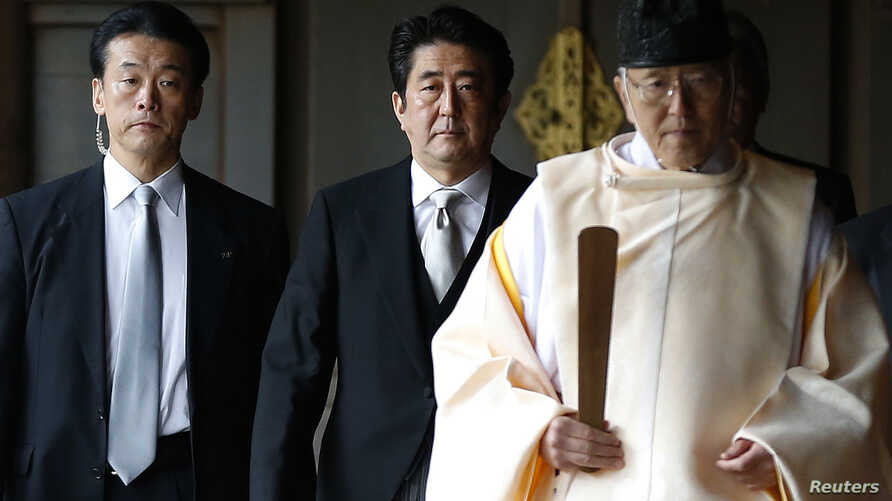 Japan's Prime Minister Shinzo Abe (C) is led by a Shinto priest as he visits Yasukuni shrine in Tokyo, Dec. 26, 2013.