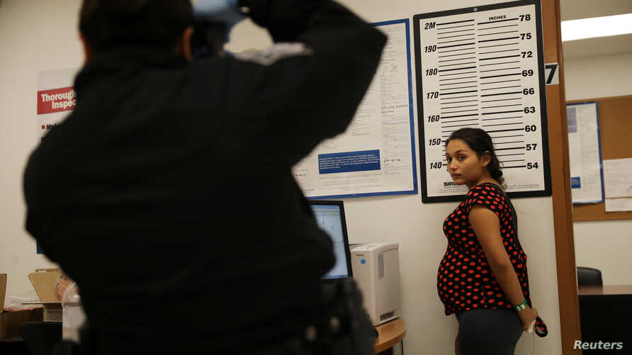 A pregnant woman who is seeking asylum has her picture taken by a U.S. Customs and Border patrol officer at a pedestrian port of entry from Mexico to the United States, in McAllen, Texas, U.S., May 10, 2017.