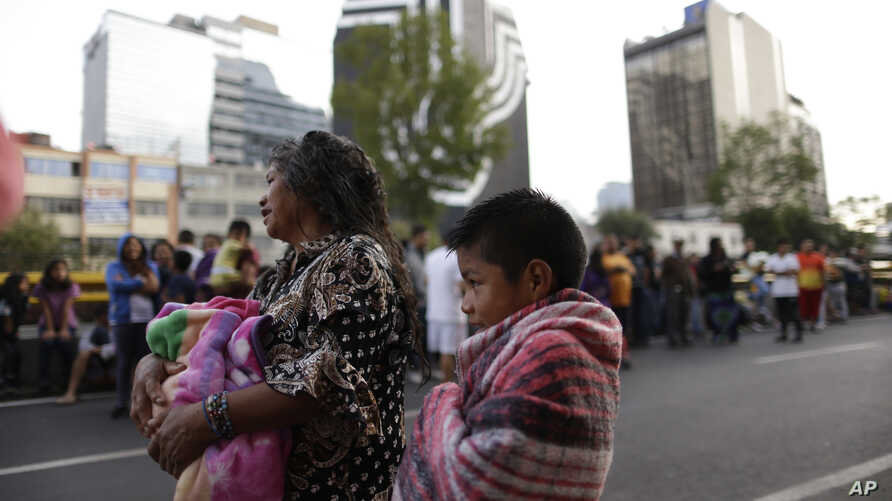 People stand in the street after hearing an earthquake alarm, in Mexico City, Saturday, Sept. 23, 2017.