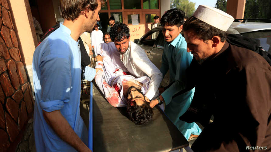 Relatives carry an injured man into a hospital after a car bomb was set off in Jalalabad, Afghanistan, June 16, 2018.