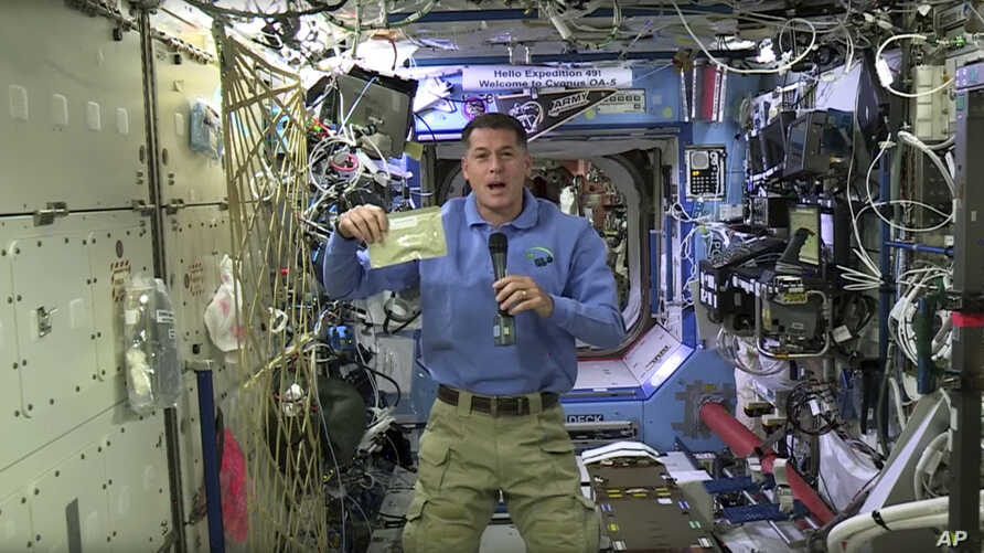 In this image taken from NASA video recorded Nov. 18, 2016, NASA astronaut Shane Kimbrough shows a pouch of turkey he will be preparing for his crew in celebration of the Thanksgiving holiday, aboard the International Space Station on Thursday, Nov.