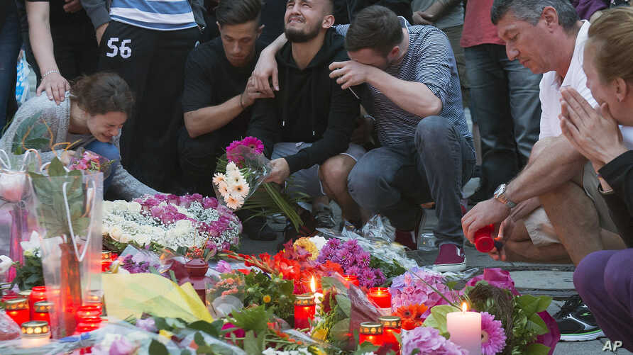 People mourn behind flower tributes near the Olympia shopping center where a shooting took place leaving nine people dead the day before, in Munich, Germany, July 23, 2016.