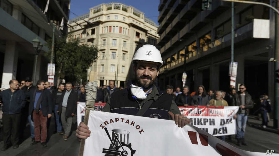 A protester from the Public Power Corporation union marches during an anti-austerity rally, in central Athens, Greece, during a 24-hour strike, Dec. 14, 2017.