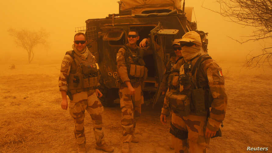 FILE - French soldiers from Operation Barkhane stand outside their armored personnel carrier during a sandstorm in Inat, Mali, May 26, 2016.