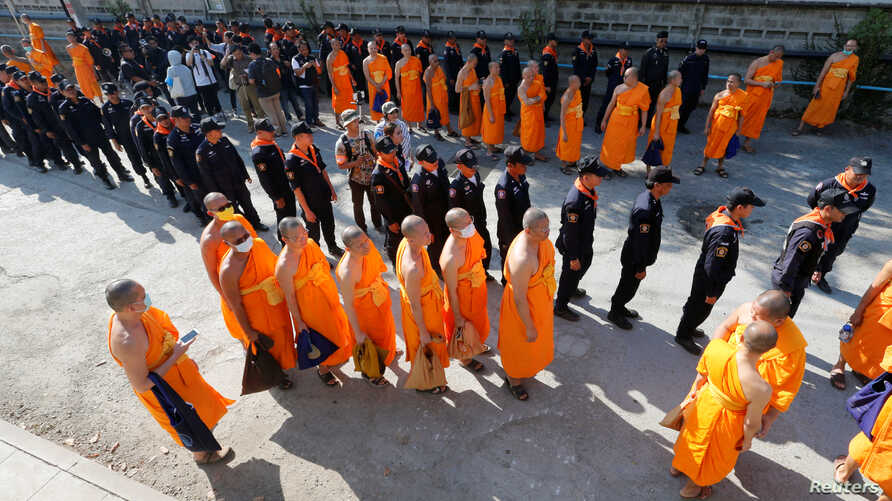 Policemen and Buddhist monks walk inside Dhammakaya temple to search for a fugitive Buddhist monk in Pathum Thani province, Thailand, Feb. 17, 2017.