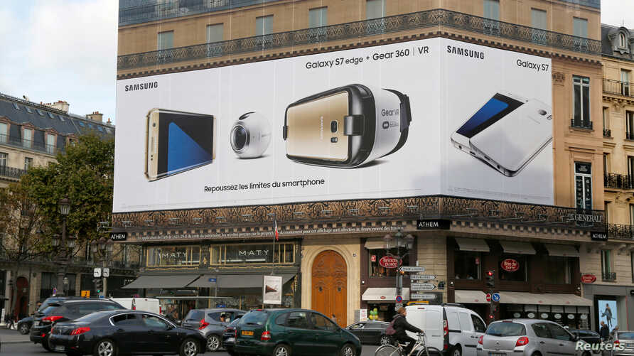 FILE - An advertisement board place de l'Opera displays a Samsung Galaxy S7 edge mobile phone, a gear VR virtual reality headset and a 360? VR Camera in Paris, France, Oct. 26, 2016.