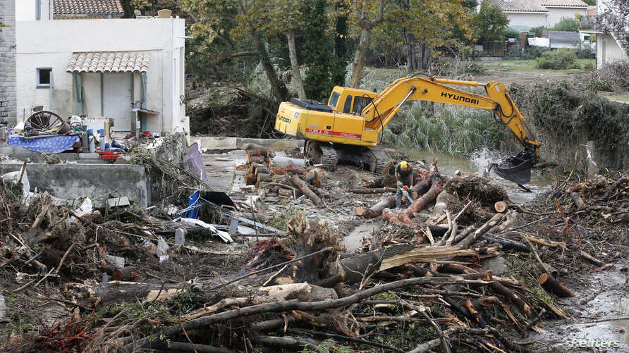 A mechanical digger clears away debris from trees in a stream near a house the day after torrential rains caused flooding in Biot, France, Oct. 5, 2015.