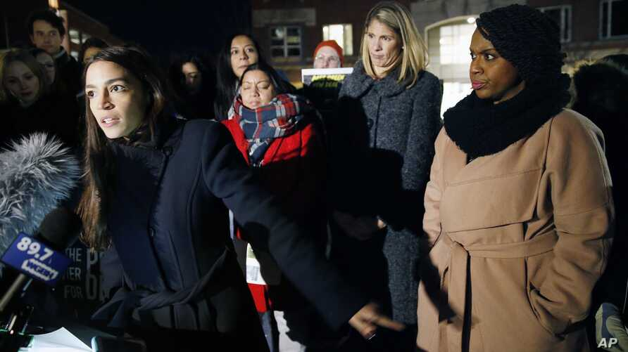 Rep.-elect Alexandria Ocasio-Cortez, D-N.Y.,, left, speaks at a small rally outside an orientation meeting for incoming members of Congress at Harvard University as Rep.-elect Ayanna Pressley, D-Mass., right, and Rep.-elect Lori Trahan, D-Mass., seco