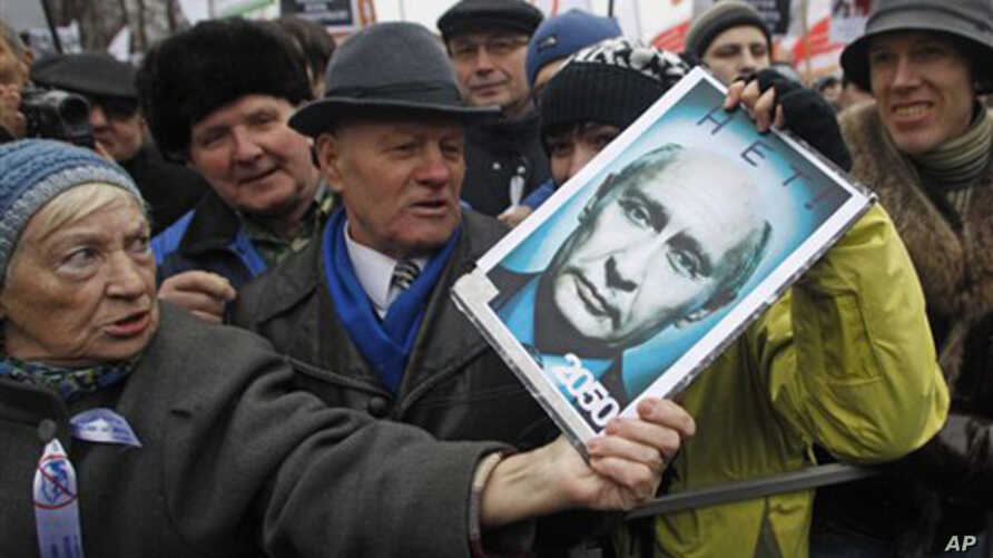 An elderly demonstrator holds a poster showing an edited photo of an aging Prime Minister Vladimir Putin and signed '2050. No'.
