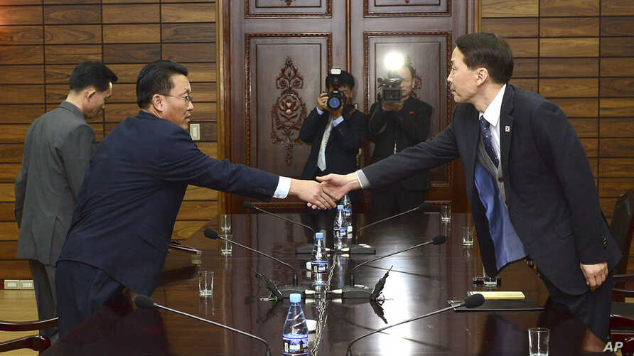 In this photo provided by the South Korean Unification Ministry, South Korea's chief delegate Kim Kiwoong, right, shakes hands with his North Korean counterpart Hwang Chol during a meeting at the border village of Panmunjom, North Korea, Thursday, No