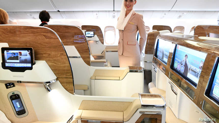 A stewardess of Emirates Airlines stands in the first class during a presentation of Emirates' Boeing 777 at the airport in Hamburg, April 11, 2018. The Dubai-based airline has already introduced virtual windows in the first-class suites of its newes