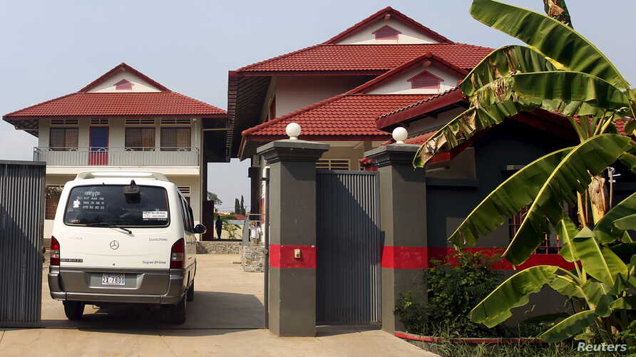 FILE - A van enters a residence that will temporarily house the first group of asylum seekers from a remote South Pacific detention centre, in Phnom Penh, Cambodia.