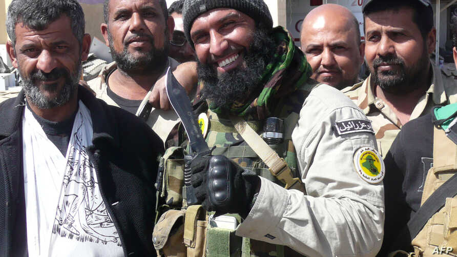 Ayyub Faleh al-Rubaie (C), known as Abu Azrael -- Father of the Angel of Death -- poses with Shiite fighters at the Speicher military base, near the northern Iraqi city of Tikrit, on March 14, 2015.