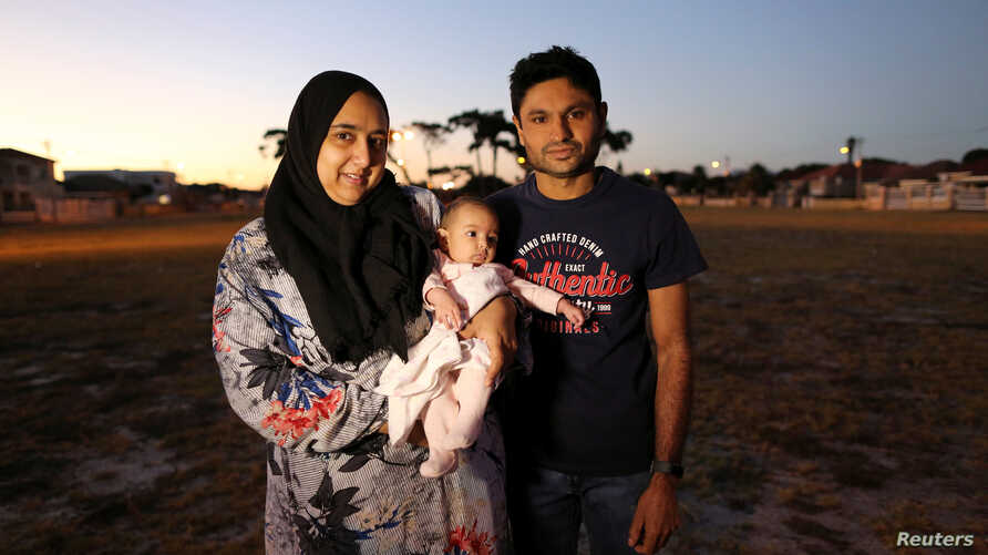 FILE - Ferzanah Essack, 36, a software developer, and her husband Hassan Essack, 37, a software developer, pose for a portrait with their 4-month-old baby Salma on the morning of Ferzanah's first day back to work, in Cape Town, South Africa, Feb. 18,