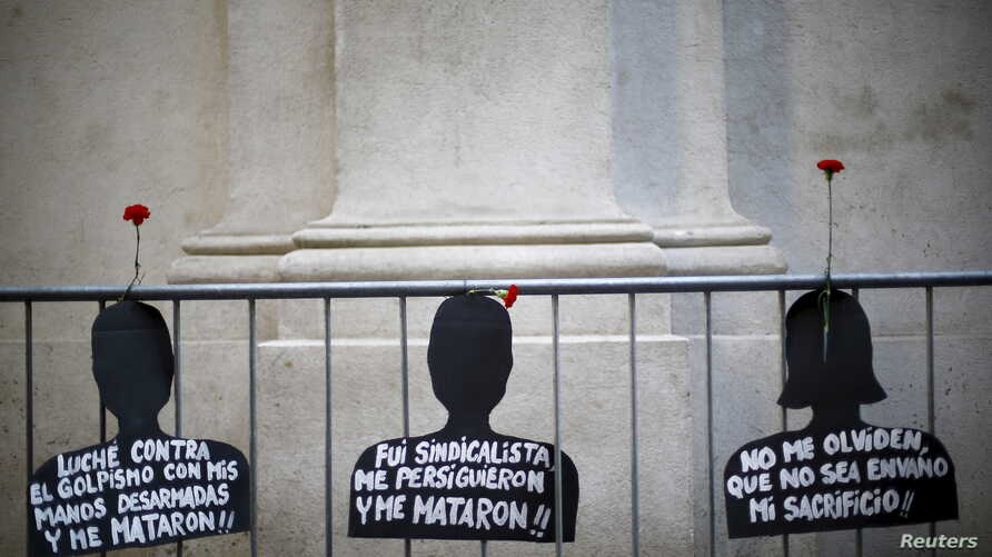 "Cut-out depicting victims of human rights abuse during the rule of former dictator Augusto Pinochet hang on a fence next to the ""La Moneda"" Presidential Palace during a rally in Santiago, Sept. 11, 2015."