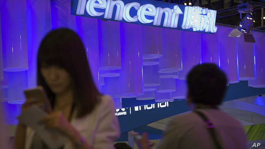 FILE - A woman uses her smartphone near a booth for the Chinese Internet company Tencent at the Global Mobile Internet Conference in Beijing, China, April 29, 2015.