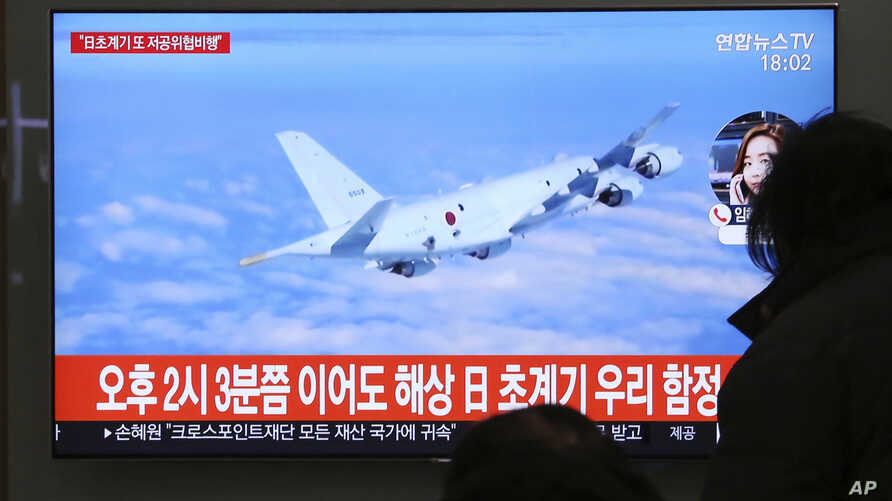 People watch a TV screen showing file footage of a Japanese patrol plane during a news program at the Seoul Railway Station in Seoul, South Korea, Jan. 23, 2019.