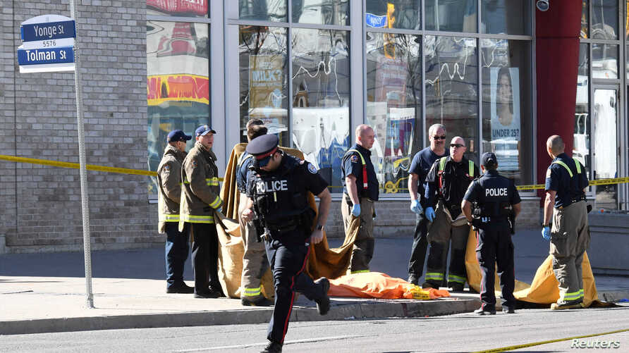 Fire fighters stand near a covered body after a van struck multiple people at a major intersection northern Toronto, Ontario, Canada, April 23, 2018.