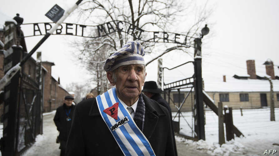 """Auschwitz survivor Miroslaw Celka walks out the gate with the sign saying """"Work makes you free"""" after paying tribute to fallen comrades at the """"death wall"""" execution spot in the former Auschwitz concentration camp in Oswiecim, Poland, on the 70th ann"""