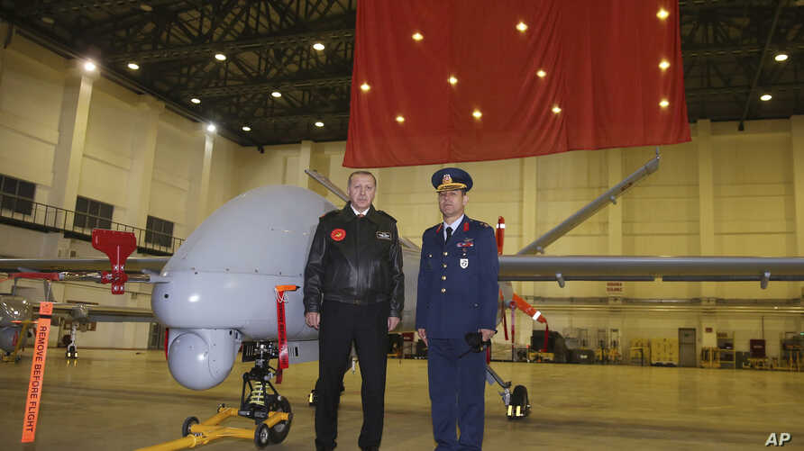 Turkey's President Recep Tayyip Erdogan poses for a photo with a Turkish army commander in front of a drone at a military airbase in Batman, Turkey, Saturday, Feb. 3, 2018.