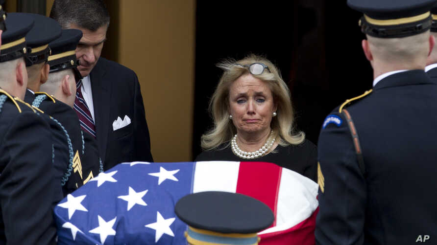 Rep. Debbie Dingell, D-Mich., watches the flag-draped casket of former Rep. John Dingell upon arrival at Holy Trinity Catholic Church for a funeral service, Feb. 14, 2019, in Washington.