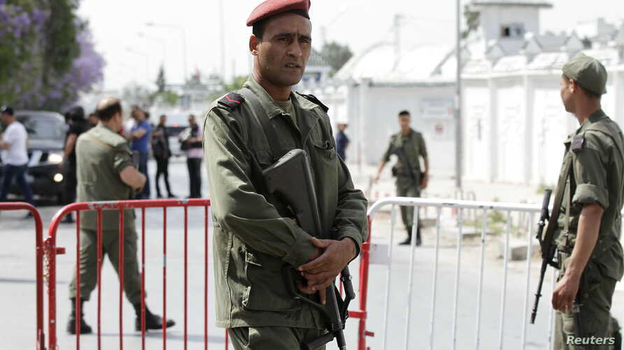 A Tunisian army officer stands guard outside the Bouchoucha military base after shooting in Tunis, Tunisia May 25, 2015.