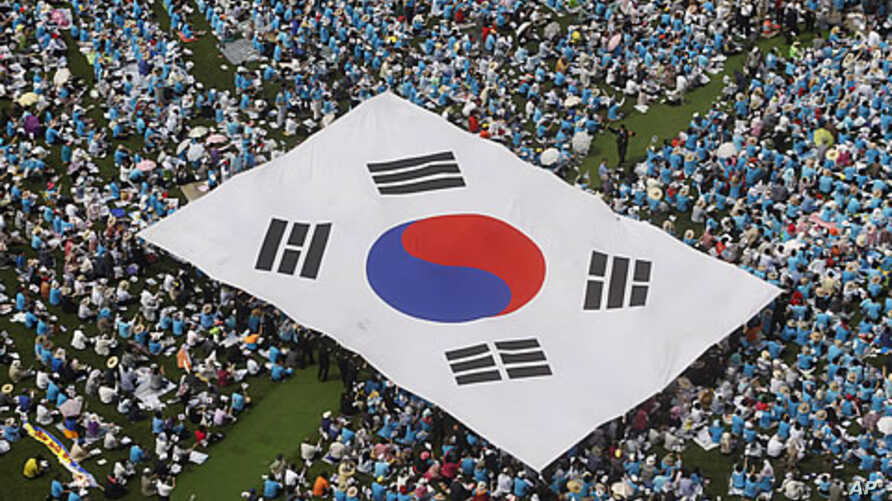 People carry a large scale South Korean national flag during an anti-North Korea rally marking Memorial Day in Seoul, June 6, 2011