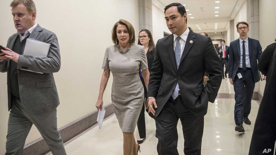 FILE - House Majority Leader Nancy Pelosi of Calif. walks with Rep. Joaquin Castro, D-Texas at the Capitol in Washington.