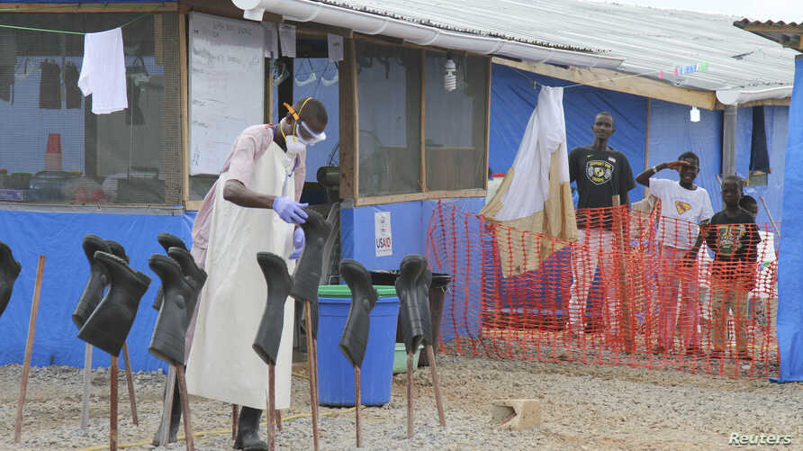 "FILE - Boys stand in the ""red zone"" where they are being treated for Ebola at the Bong County ebola treatment unit about 200 km east of Monrovia, Liberia, Oct. 28, 2014."