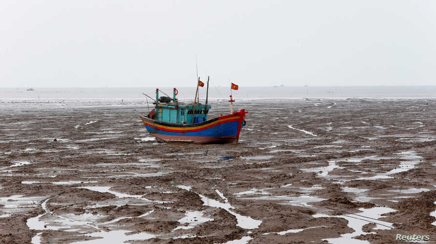 A fishing boat is seen during the low tide at the beach in Thanh Hoa province, Vietnam June 4, 2018.