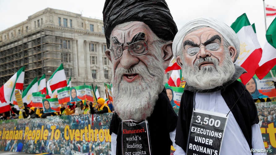 FILE - Protesters yell behind effigies of Iranian President Hassan Rouhani and Supreme Leader Ayatollah Ali Khamenei to rally for government change in Iran during a demonstration in Washington, March 8, 2019.