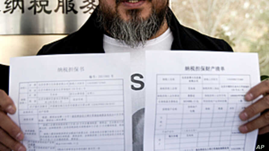 Chinese dissident artist Ai Weiwei shows his tax guarantee slips as he leaves the the Beijing Local Taxation Bureau, China. Ai went to the local tax bureau to fill in paperwork for a $1.3 million guarantee, and told reporters he feels like he was pay