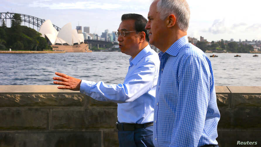 Australia's Prime Minister Malcolm Turnbull walks with Chinese Premier Li Keqiang along the Sydney Harbor in front of the Sydney Opera House in Australia, March 25, 2017.