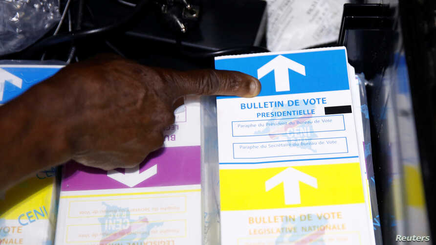 An agent of Congo's National Independent Electoral Commission points at ballots before voting starts at a poling station in Kinshasa, Democratic Republic of Congo, Dec. 30, 2018.